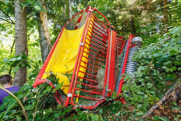 Heu-Schlepper rollt Hang hinunter und kracht in Wald
